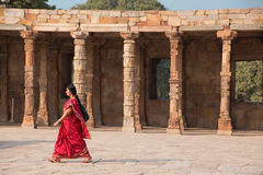 Indian woman walking through courtyard of Quwwat-Ul-Islam mosque Royalty Free Stock Photos