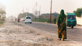 Indian woman walking on the road Royalty Free Stock Photography
