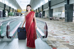 Indian woman walks in the airport terminal. Pretty Indian woman wearing saree clothes and walks in the airport terminal while carrying a suitcase Royalty Free Stock Photography