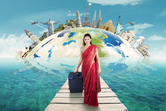 Indian woman walks on the jetty carrying bag Stock Images