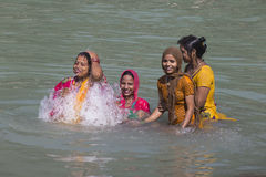 Indian woman wash themselves in the river Ganges  in the holy city of Rishikesh, India. Royalty Free Stock Images