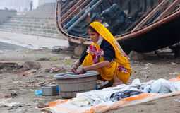Indian woman washes clothes on ghat near sacred river Ganges in Varanasi Royalty Free Stock Photo