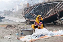 Indian woman washes clothes on ghat near sacred river Ganges in Varanasi Stock Photo
