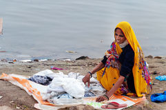 Indian woman washes clothes on ghat near sacred river Ganges in Varanasi Stock Images