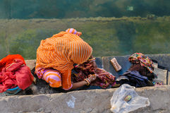 An Indian woman washes clothes in the river Ganges Stock Photos