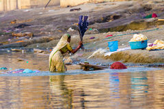 Indian woman washes in the river. Women washing their saris and clothing in holy Ganga river, Haridwar, India Stock Images