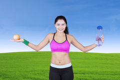 Indian woman with water bottle and apple Stock Photography
