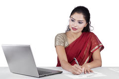 Indian woman working with laptop while writing stock photos