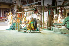 Indian woman working with rug material Stock Photos
