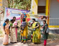 Indian women before advertising posters. India, Varkala. - January 05, 2016; Group of women dressed in Sari and children. Indian women before advertising posters Royalty Free Stock Photo