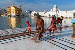 Indian women and children clean floor near Golden Temple before the evening prayer. Amritsar Royalty Free Stock Photo