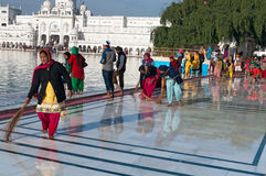Indian women clean floor near Golden Temple before the evening prayer. Amritsar Stock Photography
