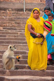 Indian women in colorful sari with a kid walking down the stairs Stock Photos