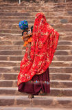 Indian women in colorful saris with a kid walking up the stairs Stock Photo