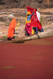 Indian women in colorful saris standing at the edge of red pond, Stock Photos