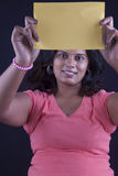 Indian women holding a yellow paper Royalty Free Stock Photo
