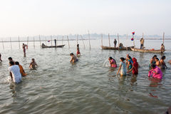 Indian women and men in the cold water. Indian women and men stand in the cold Sangam water at time of celebration Paush Purnima during the biggest hindu Stock Photos