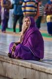 Indian women in purple sari sitting near the lake at Golden Temple. Amritsar. India Royalty Free Stock Photos