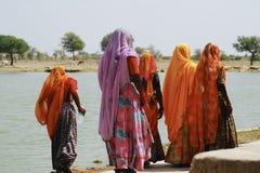 Indian women in saris next to lake in Jaisalmer, India. Indian women in saris walking next to a lake in Jaisalmer, India Royalty Free Stock Photo