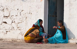 Indian women sit and chat on a house porch Royalty Free Stock Image