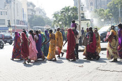 Indian women walking on the street. Mumbai, India. Group of Indian women walking through the streets of Mumbai. Colorful traditional dresses. Traffic through the stock images
