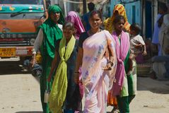 Indian women wearing colorful sarees walk by the street in Orchha, India. stock photos