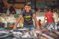 Indian worker. MUMBAI, INDIA - 08 JANUARY 2015: Worker on a fishmarket poses while waiting for customers. Post-processed with grain, texture and colour effect royalty free stock photo
