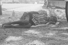 Indian worker sleeping on road. Indian worker sleeping on the side of the road with his carrier behind him he is resting cause of the work and the heat stock photo
