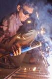 Indian worker welding. KAMALAPURAM, INDIA - 02 FABRUARY 2015: Indian worker welding heavy metal parts on street in dusk Stock Photography