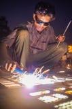 Indian worker welding. KAMALAPURAM, INDIA - 02 FABRUARY 2015: Indian worker welding heavy metal parts on street in dusk Royalty Free Stock Image