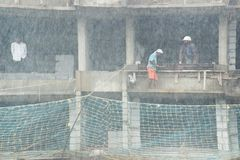Indian workers at a construction site on a heavy rainy day