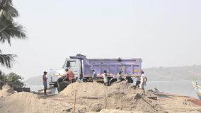 Indian workers load sand into a truck with shovels stock footage