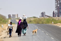 Indian workers walking past industries Royalty Free Stock Photo