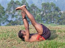 Indian yoga teacher doing yoga exercise. On green grass in Kerala, South India Royalty Free Stock Photography