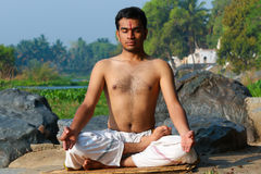 Indian Yogi. Indian man practicing yoga meditation next to a river in South India royalty free stock images