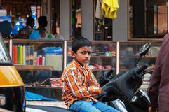 Indian young boy sitting on the bike at the Russell market in Bangalore Royalty Free Stock Photo