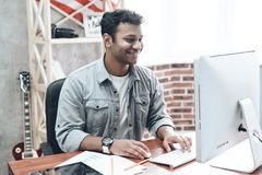Indian Young Businessman Work on Computer on Table. Handsome Indian Young Businessman Work on Computer on Table. Cheerful Smiling Man in Coat Sits in Front of stock images