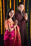 Indian young couple in ethnic wear in namaskara pose. Portrait of Maharashtrian couple holding a puja thali, indian couple holding puja thali or pooja thali Royalty Free Stock Photo