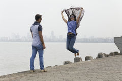 Indian young couple at Marine Drive Mumbai India girl jumping with her scarf. Royalty Free Stock Images