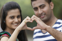 Indian young couple at Marine Drive Mumbai India holding hands showing love sign. Stock Image