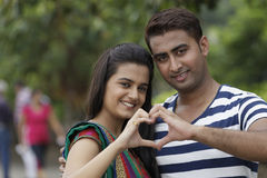 Indian young couple at Marine Drive Mumbai India holding hands showing love sign. Royalty Free Stock Photo