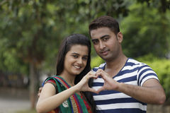 Indian young couple at Marine Drive Mumbai India holding hands showing love sign. Stock Photo