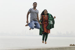 Indian young couple at Marine Drive Mumbai India jumping. Stock Images