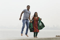 Indian young couple at Marine Drive Mumbai India jumping. Royalty Free Stock Image