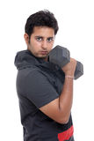 Indian young man curling a dumbbell Royalty Free Stock Photo
