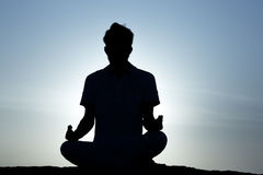 Indian Young man practicing yoga on the mountain at blue sunset. Indian Young man practicing yoga on the high mountain at blue sunset stock image