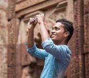 Indian young man take a mobil photo of local architect sight stock image