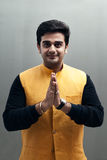 Indian young man in welcome posture. Portrait of handsome indian young man doing welcome and regards by joining their hand Royalty Free Stock Photography
