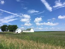 Indiana farm with green and white barn under a blue sky. A rural scene in Indiana of a green and white barn and farm buildings under a blue sky with clouds on a stock photo