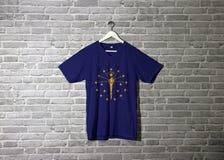 Indiana flaga na koszula i obwieszenie na ścianie z cegłą deseniujemy tapetę obraz stock